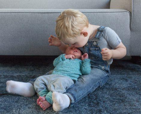 newborn Fotograaf Heerhugowaard, baby krijgt kus van broer, fotografie, babyfotografie, pasgeboren